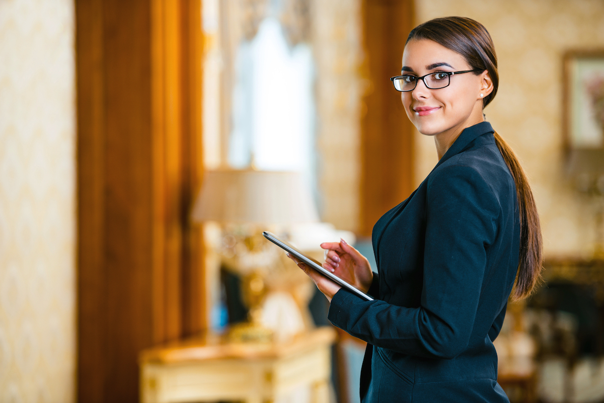 Photo of business woman in expensive hotel. Young business woman wearing suit and glasses, standing in nice hotel room, using tablet computer and looking at camera